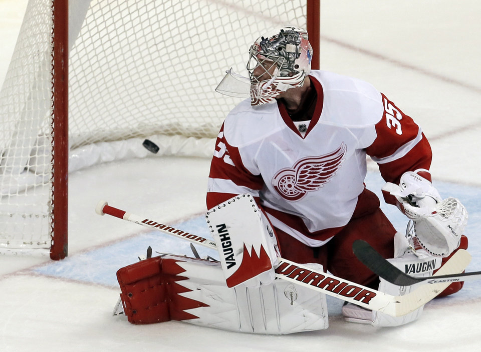 Photo - Detroit Red Wings goalie Jimmy Howard (35) watches as Dallas Stars forward Rich Peverley's (17)shot sails past into the net in the first period of an NHL hockey game, Saturday, Jan. 4, 2014, in Dallas. (AP Photo/Brandon Wade)