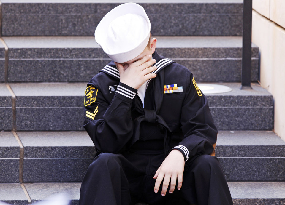 Photo -  Zackary Kirkham, 13 of Sparks, Okla. and a member of the US Naval Sea Cadet Corp, covers his face as he sits on the steps while the names of the victims were read at the 19th anniversary Remembrance Ceremony at the Oklahoma City National Memorial Saturday morning, April 19, 2014, to honor the memory of the 168 victims killed in the 1995 bombing of the Murrah Federal Building. Photo by KT King, The Oklahoman