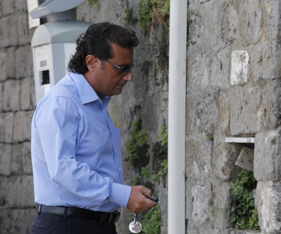 Photo -   Francesco Schettino, the former captain of Costa Concordia, leaves his home in Meta Di Sorrento, near Naples, Sunday, Oct. 14, 2012. The first hearing of the trial for the Jan. 13 tragedy, where 32 people died after the luxury cruise Costa Concordia was forced to evacuate some 4,200 passengers as it hit a rock while passing too close to the Giglio Island, is taking place in Grosseto Monday. Captain Francesco Schettino, who was blamed for both the accident and for leaving the ship before the passengers, is scheduled to attend the hearing. (AP Photo/Salvatore Laporta)