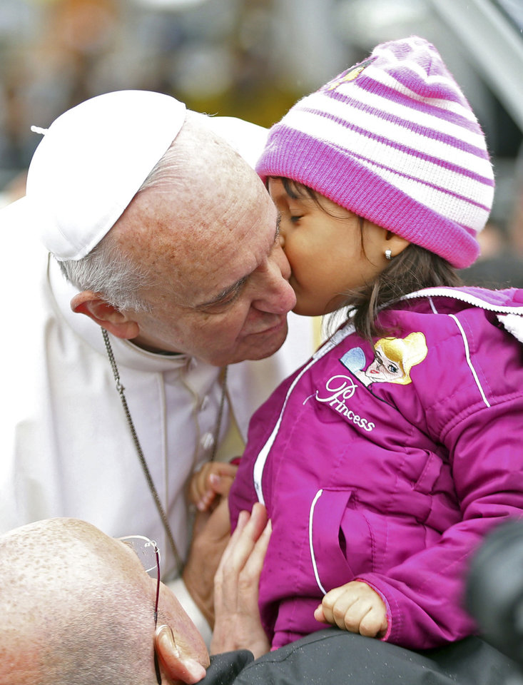 Photo - Pope Francis kisses a child as he arrives in his popemobile to the Aparecida basilica in Aparecida, Brazil, Wednesday, July 24, 2013. Tens of thousands of faithful flocked to the tiny town of Aparecida, tucked into an agricultural region halfway between Rio de Janeiro and Sao Paulo, where he is to celebrate the first public Mass of his trip in a massive basilica dedicated to the nation's patron saint. (AP Photo/Victor R. Caivano)