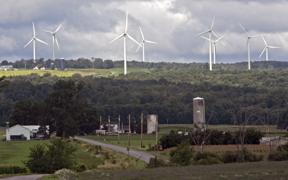 FILE--In this Aug. 4, 2008 file photo, wind turbines from the Maple Ridge Wind Farm tower over farms in Martinsburg, N.Y. A new study says New York could be completely powered by wind, water and sunlight by 2030 with a concerted push, though the state's own decade-long effort to significantly boost green energy shows how difficult that would be in practice. (AP Photo/Mike Groll, File)