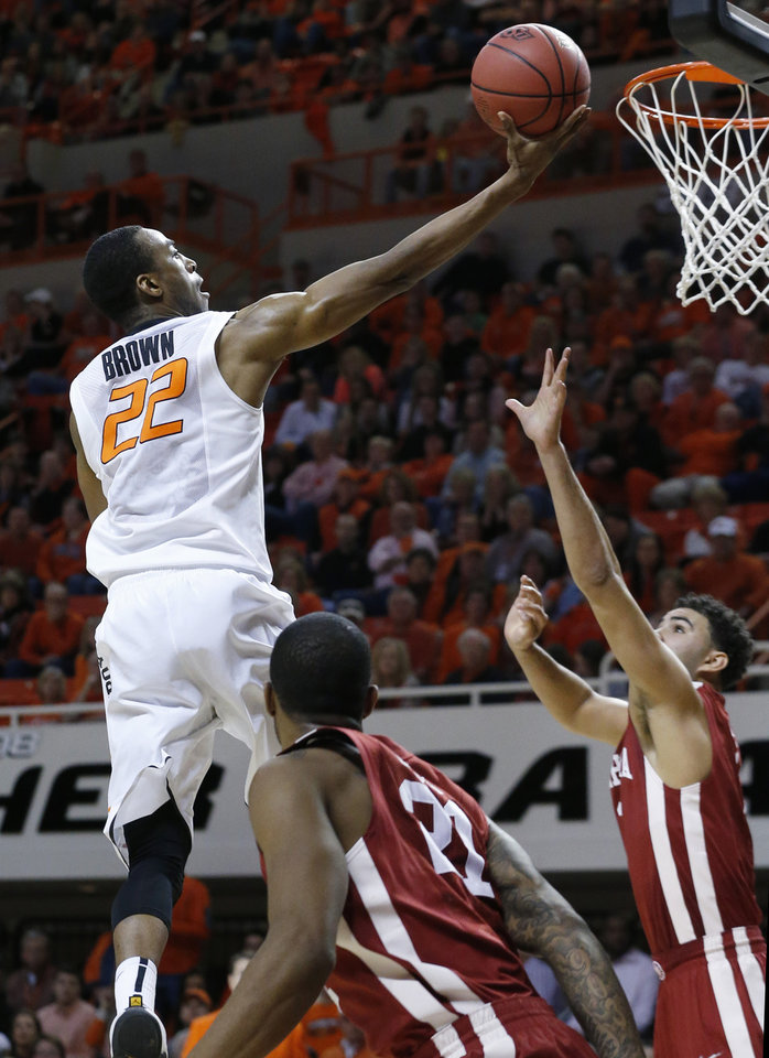 Photo - Oklahoma State wing Markel Brown (22) shoots between Oklahoma guard Cameron Clark (21) and  guard Frank Booker (1) in the second half of an NCAA college basketball game in Stillwater, Okla., Saturday, Feb. 15, 2014. Oklahoma won 77-74. (AP Photo/Sue Ogrocki)