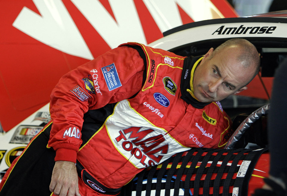 Photo - Driver Marcos Ambrose retrieves something from his car before the start of a practice session for Saturday night's NASCAR Sprint Cup series auto race at Kentucky Speedway in Sparta, Ky., Friday, June 28, 2013. (AP Photo/Garry Jones)