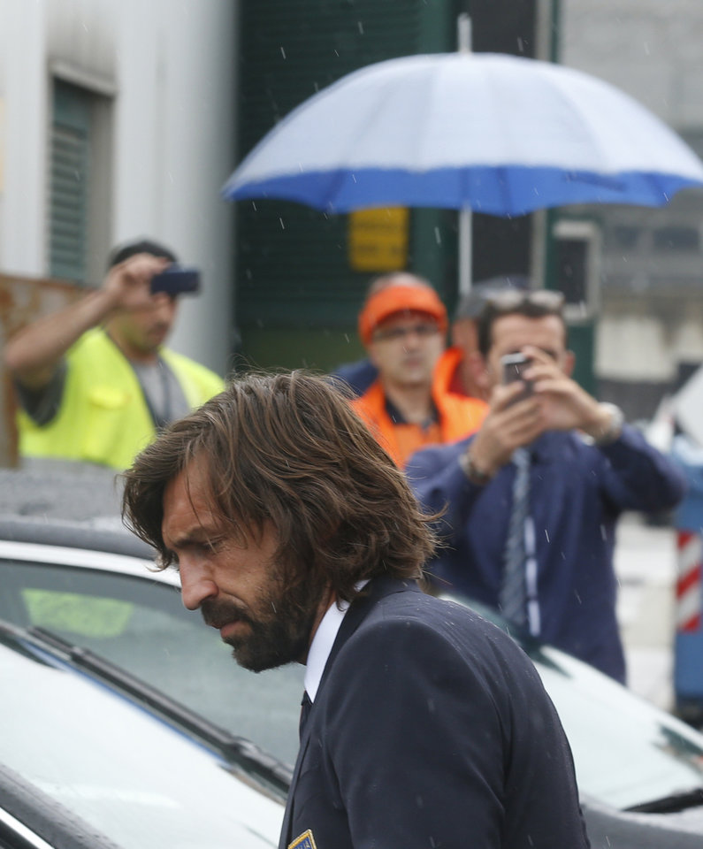 Photo - Italy soccer player Andrea Pirlo carries his luggage upon his arrival with his teammates at Malpensa airport after landing from Brazil, in Milan, Italy, Thursday, June 26, 2014.Pirlo recently quit the national team. Pirlo had said before the tournament he would quit international football after Brazil. Italy was disqualified from the World Cup after loosing to Uruguay in their group stage round.  (AP Photo/Luca Bruno)
