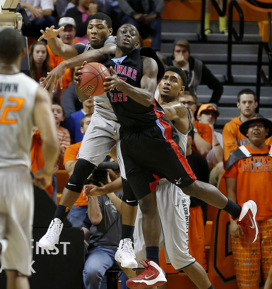 Oklahoma State's Marcus Smart (33) leaps for the ball beside Delaware State's Ashwell Boyd (45) as Le'Bryan Nash (2) watches during an NCAA college basketball between Oklahoma State University and Delaware State at Gallagher-Iba Arena in Stillwater, Okla., Tuesday, December 17, 2013. Oklahoma State won 75-43. Photo by Bryan Terry, The Oklahoman