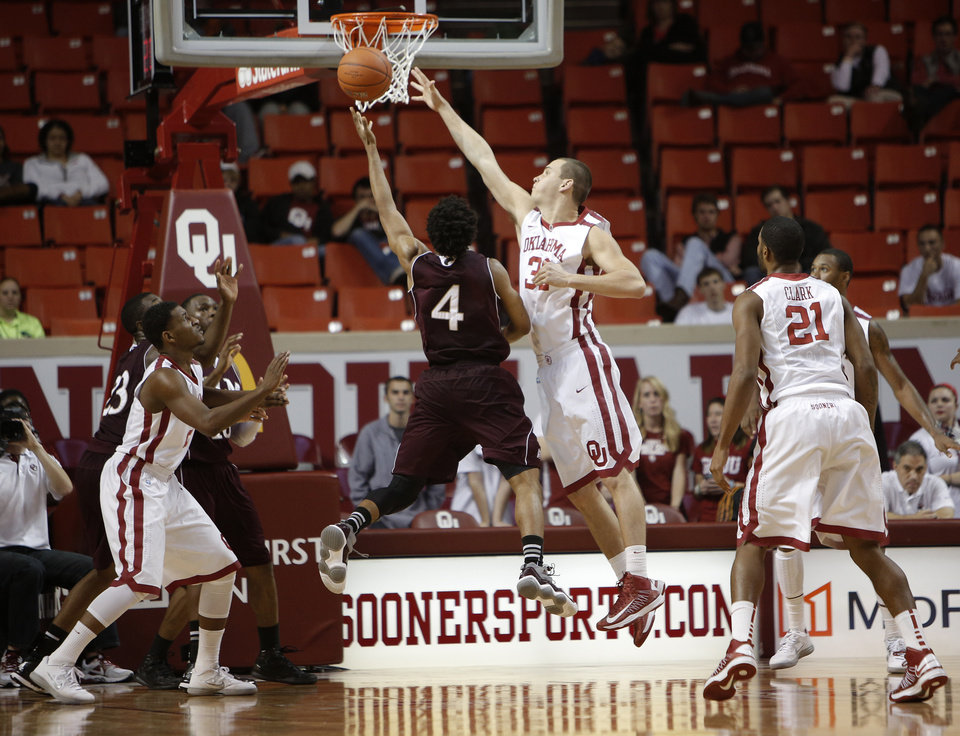 Photo - Oklahoma's Casey Arent (32) blocks a shot by Louisiana's R.J. McCray (4) during a men's college basketball game between the University of Oklahoma and the University of Louisiana-Monroe at the Loyd Noble Center in Norman, Okla., Sunday, Nov. 11, 2012.  Photo by Garett Fisbeck, The Oklahoman