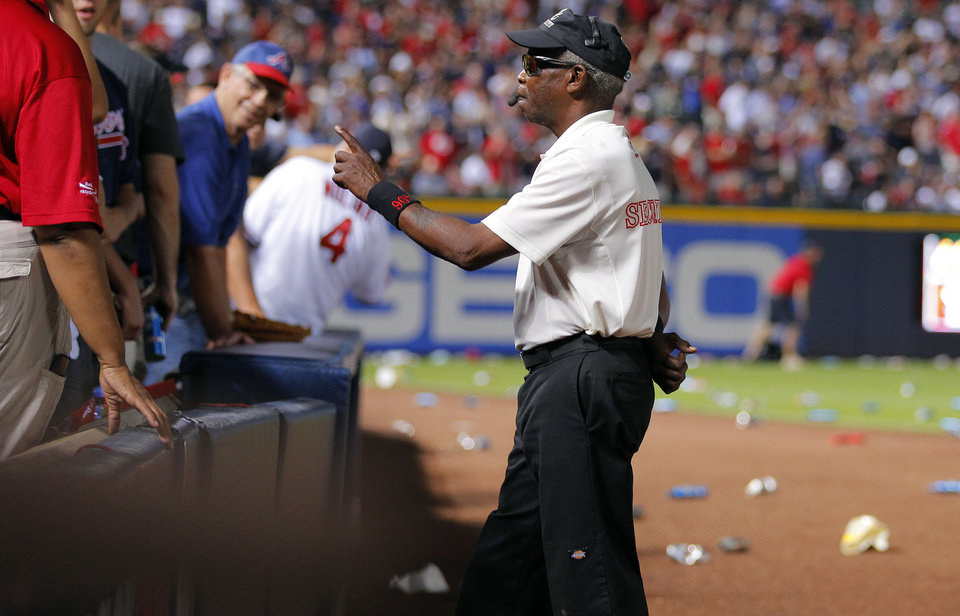 Photo -   A security official shouts to fans to not throw trash on the field during the eighth inning of the National League wild card playoff baseball game between the Atlanta Braves and the St. Louis Cardinals, Friday, Oct. 5, 2012, in Atlanta. The Cardinals won baseball's first wild-card playoff, taking advantage of a disputed infield fly call that led to a protest and fans littering the field with debris to defeat the Braves 6-3. (AP Photo/Todd Kirkland)