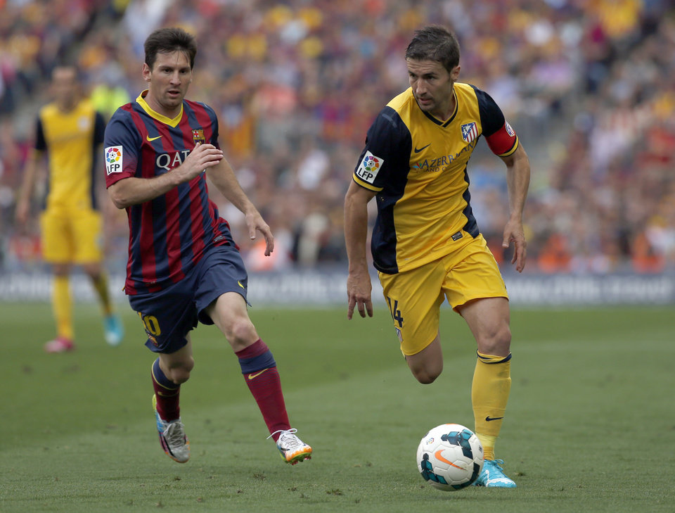 Photo - Barcelona's Lionel Messi from Argentina, left, and Atletico's Gabi challenge for the ball during a Spanish La Liga soccer match between FC Barcelona and Atletico Madrid at the Camp Nou stadium in Barcelona, Spain, Saturday, May 17, 2014. (AP Photo/Emilio Morenatti)