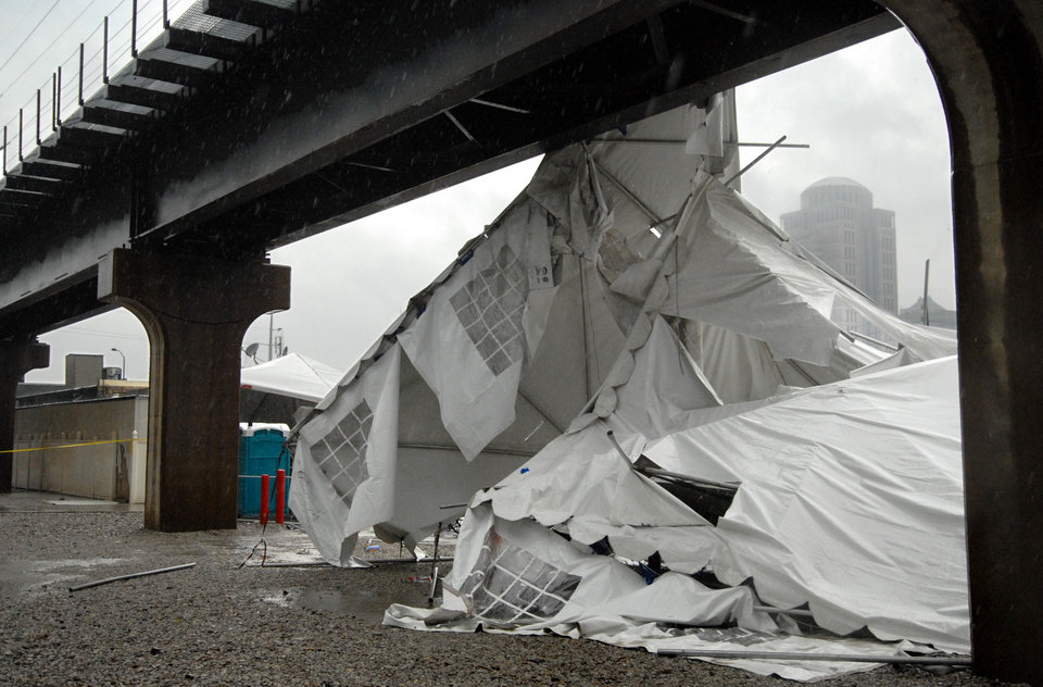Photo -   A party tent from Kilroy's Sports Bar in St. Louis rests against a railroad trestle near the bar after storm winds blew through the area following a baseball game between the St. Louis Cardinals and Milwaukee Brewers at nearby Busch Stadium Saturday, April 28, 2012. One person died Saturday and more than a dozen were taken to a hospital with injuries after high winds blew over a beer tent near Busch Stadium in St. Louis. (AP Photo/Sid Hastings)