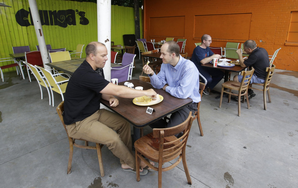 Photo - In this July 29, 2014, photo, patrons eat on the patio at the Chunga's Mexican Grill, in Salt Lake City. The hunt for a taste of Mexico City brings diners near a highway overpass in a neighborhood known for tire shops and tacos. (AP Photo/Rick Bowmer)