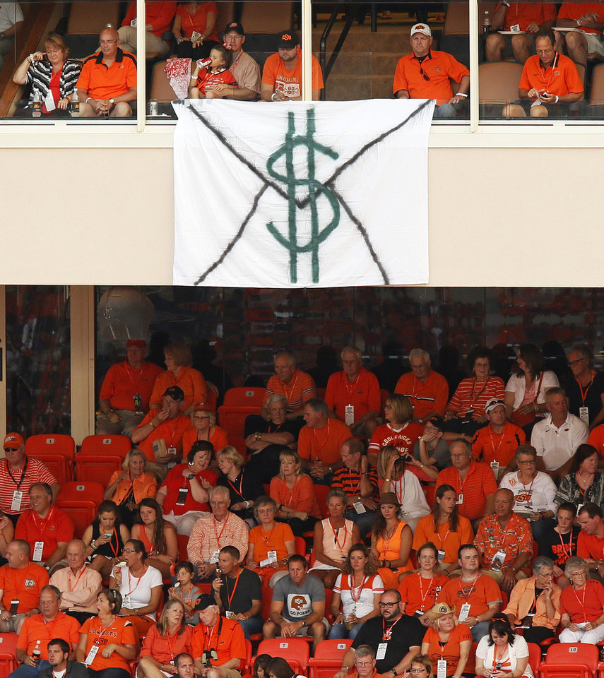 Photo - A banner painted to look like an envelope with money hangs from a suite during a college football game between the Oklahoma State University Cowboys (OSU) and the Lamar University Cardinals at Boone Pickens Stadium in Stillwater, Okla., Saturday, Sept. 14, 2013. Photo by Nate Billings, The Oklahoman