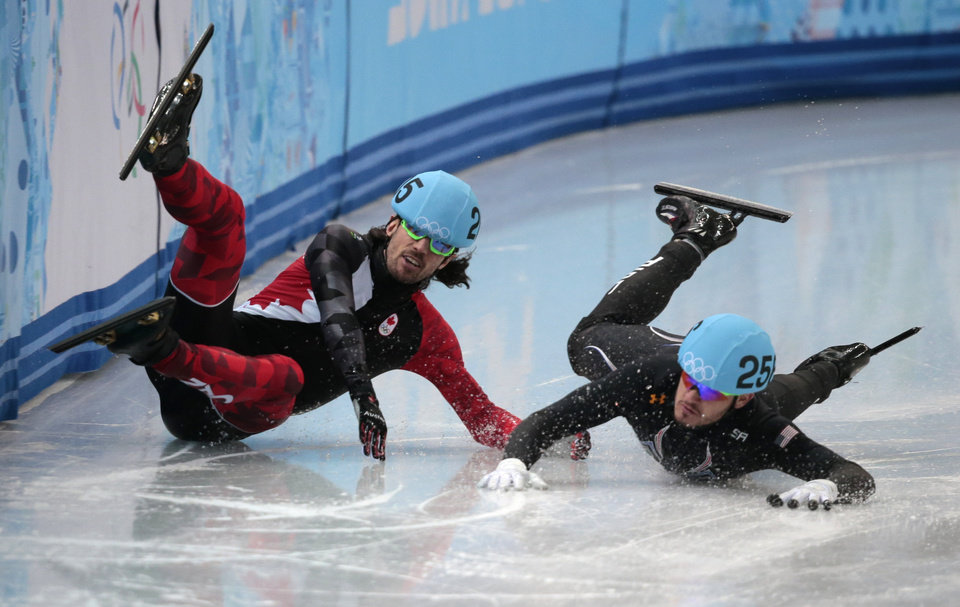 Photo - Eduardo Alvarez of the United States, right, and Charles Hamelin of Canada crash out in a men's 1000m short track speedskating quarterfinal at the Iceberg Skating Palace during the 2014 Winter Olympics, Saturday, Feb. 15, 2014, in Sochi, Russia. (AP Photo/Ivan Sekretarev)