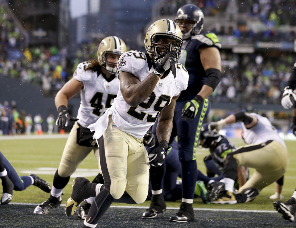 Photo - New Orleans Saints running back Khiry Robinson (29) celebrates after running for a 1-yard touchdown during the fourth quarter of an NFC divisional playoff NFL football game against the Seattle Seahawks in Seattle, Saturday, Jan. 11, 2014. (AP Photo/Elaine Thompson)