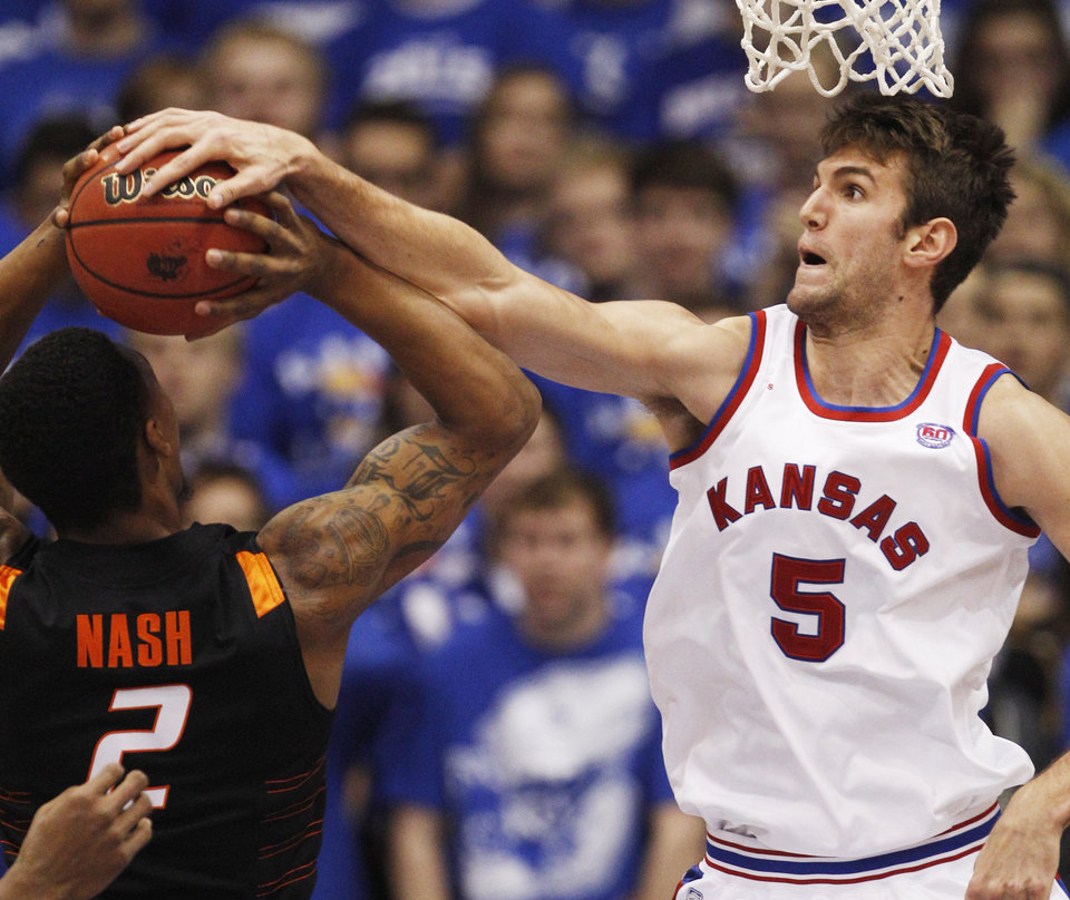 Kansas center Jeff Withey (5) fouls Oklahoma State guard/forward Le'Bryan Nash (2) during the first half of an NCAA college basketball game in Lawrence, Kan., Saturday, Feb. 11, 2012. (AP Photo/Orlin Wagner) ORG XMIT: KSOW101
