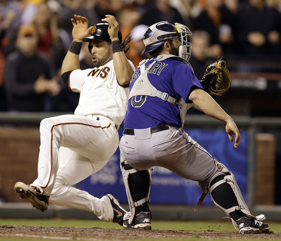 Photo - San Francisco Giants' Angel Pagan, left, slides to score past Colorado Rockies catcher Michael McKenry in the seventh inning of a baseball game Wednesday, Aug. 27, 2014, in San Francisco. Pagan scored on a single by Buster Posey. (AP Photo/Ben Margot)