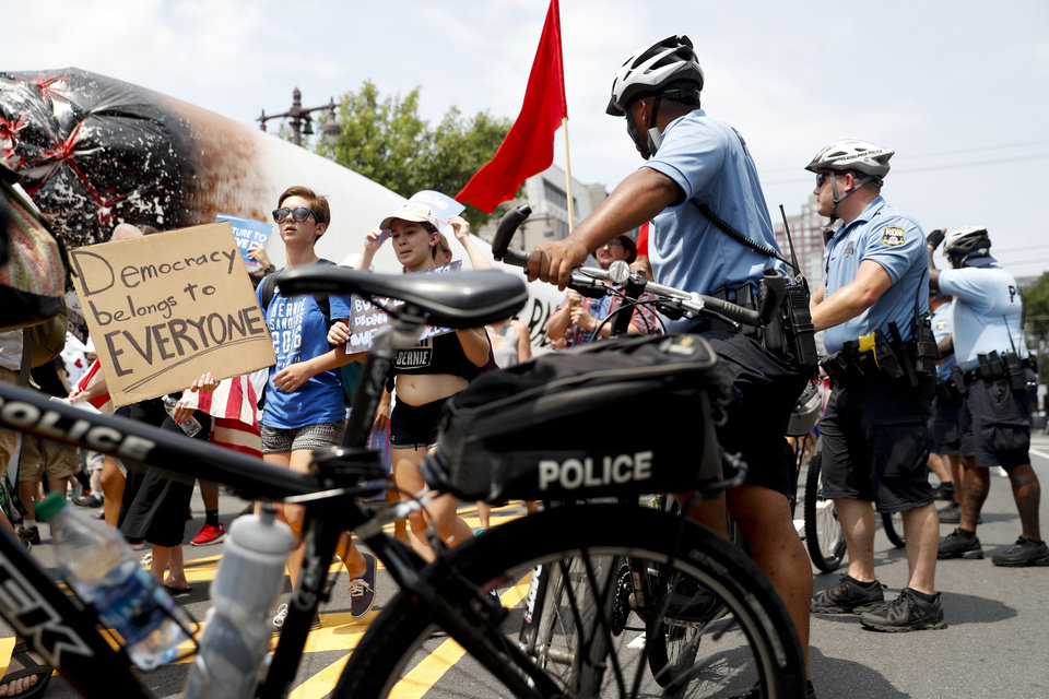 Photo - Demonstrators make their way around downtown as police officers look on, Monday, July 25, 2016, in Philadelphia, during the first day of the Democratic National Convention. (AP Photo/John Minchillo)