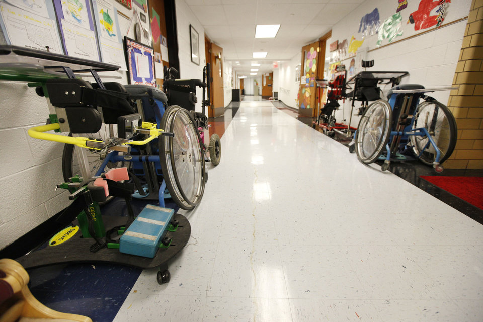 Photo - Various types of assistive chairs are lined up in the hallway at Johnson Elementary School. Photo by Paul Hellstern, The Oklahoman  PAUL HELLSTERN - Oklahoman