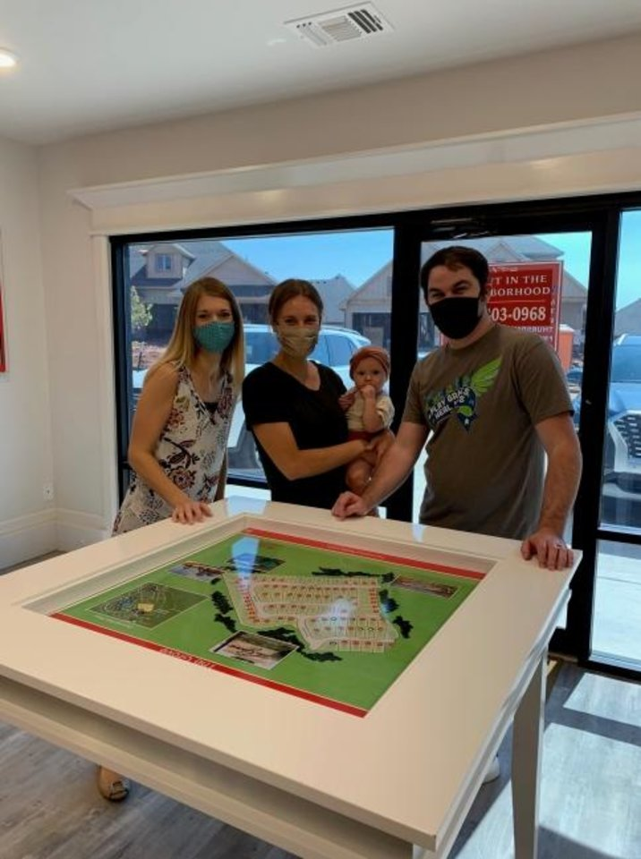 Photo -  Realtor Leah Brown and Megan and Gary Mayden, and baby Norah, look at home sites on a model at Homes by Taber. [PHOTO PROVIDED]