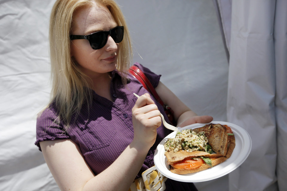Photo - Kate Janke eats a Zucchini, Cheese, Tomato & Basil Jaffle w/Lentil Tabouli Salad from the Australian Jaffles and Salads & KCSC-FM booth on International Food Row during the Festival of the Arts in downtown Oklahoma City, Wednesday, April 25, 2012. Photo by Nate Billings, The Oklahoman