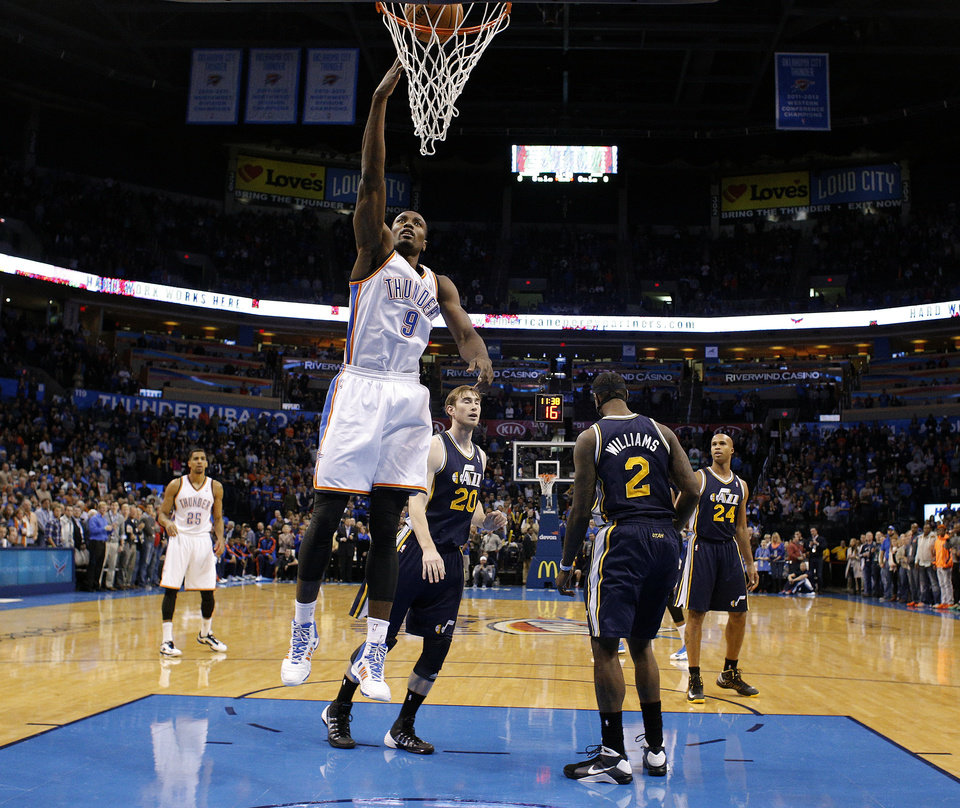 Photo - Oklahoma City's Serge Ibaka (9) shoots a lay up in front of Gordon Hayward (20) and Marvin Williams (2) during the NBA game between the Oklahoma City Thunder and the Utah Jazz at the Chesapeake Energy Arena, Sunday, Nov. 24, 2013. Photo by Sarah Phipps, The Oklahoman