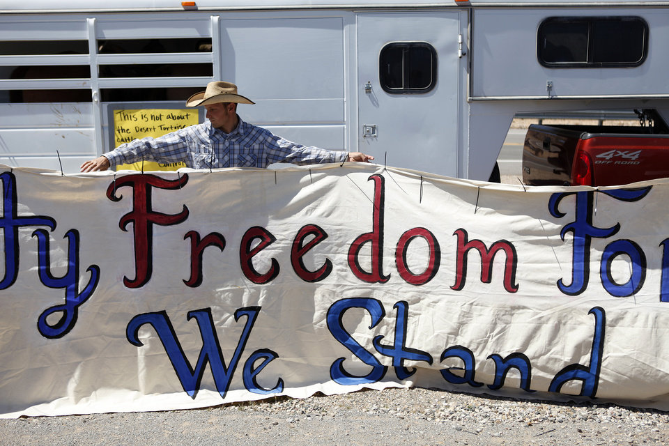 Photo - John Banks holds up a banner during a rally in support of Cliven Bundy near Bunkerville Nev. Monday, April 7, 2014, 2014. The Bureau of Land Management has begun to round up what they call