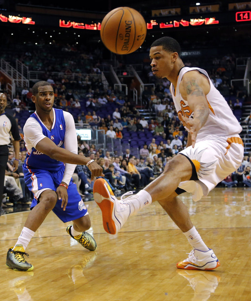 Photo - Los Angeles Clippers' Chris Paul, left, passes around Phoenix Suns' Gerald Green during the first half of an NBA basketball game, Tuesday, March 4, 2014, in Phoenix. (AP Photo/Matt York)