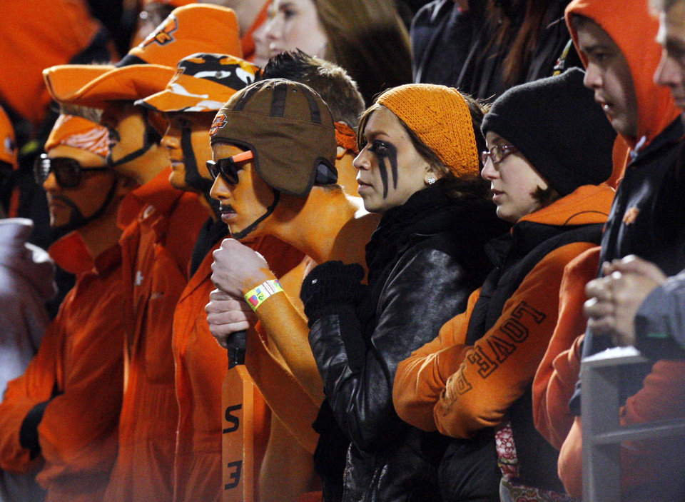 Photo - OSU fans are silent after an OU score late in the fourth quarter during the Bedlam college football game between the University of Oklahoma Sooners (OU) and the Oklahoma State University Cowboys (OSU) at Boone Pickens Stadium in Stillwater, Okla., Saturday, Nov. 27, 2010. OU won, 47-41. Photo by Nate Billings, The Oklahoman