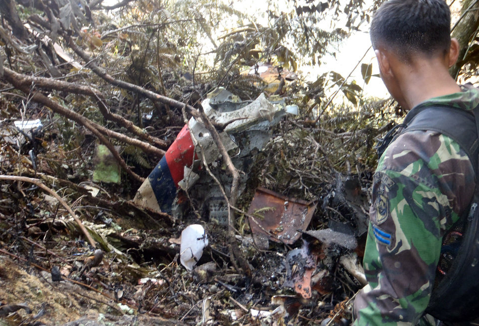 Photo -   In this May 11, 2012 photo released by volunteer group Relawan 37, an Indonesian Marine looks at the wreckage of Sukhoi Superjet-100 on Mount Salak in Bogor, Indonesia. Search teams who scaled the volcano's steep slopes found at least 12 bodies Friday near the wreckage of the Russian-made jetliner that crashed in Indonesia during a demonstration flight for potential buyers, an official said. All 45 aboard the Sukhoi Superjet-100 that crashed Wednesday are feared dead. (AP Photo/ Relawan 37, Duyeh)