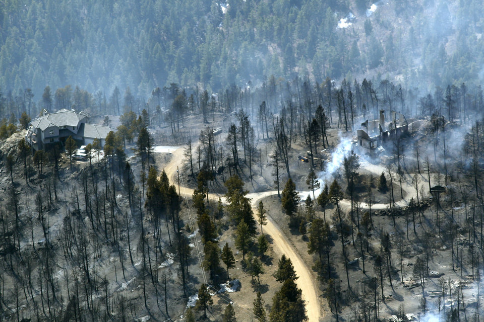 Photo -   FILE - In this March 27, 2012 photo, one home stands untouched at left while another home at right smolders after burning in the Lower North Fork Wildfire in the foothills community of Conifer, Colo., southwest of Denver. Emergency officials told confused residents not to worry after they reported a fire on the outskirts of Denver, including at least two residents who later were found dead in their burning home, 911 calls released by officials Tuesday showed. (AP Photo/David Zalubowski, File)