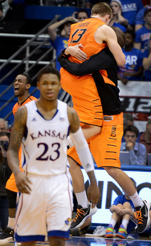 Photo - Oklahoma State's Markel Brown, left rear, and Phil Forte, who was jumping into the arms of a teammate after the final buzzer sounded on the Cowboys' 85-80 upset win over Ben McLemore (23) and Kansas at Allen Fieldhouse in Lawrence, Kansas, on Saturday, February 2, 2013. (Rich Sugg/Kansas City Star/MCT)