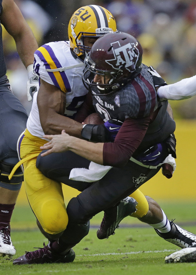 Photo - Texas A&M quarterback Johnny Manziel (2) is tackled by LSU defensive end Danielle Hunter (94) in the first half of an NCAA college football game in Baton Rouge, La., Saturday, Nov. 23, 2013. (AP Photo/Gerald Herbert)
