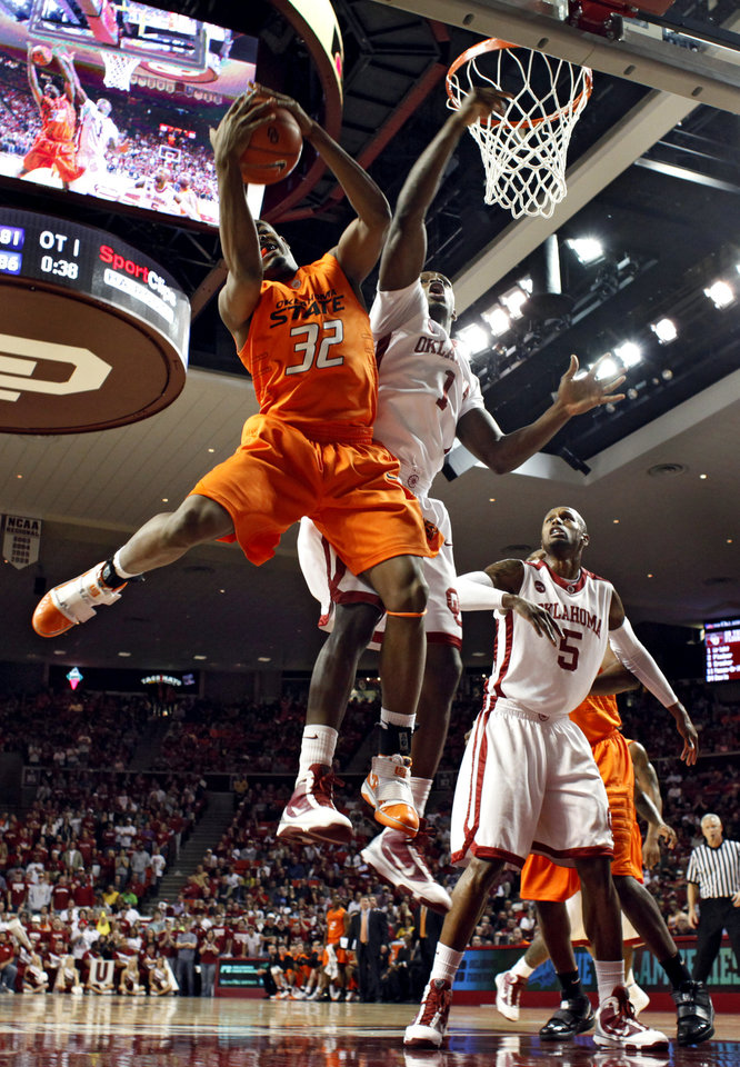 Photo - OU's Ryan Wright (1) and OSU's Roger Franklin (32) battle under the basket during the first half of the college bedlam basketball game between The University of Oklahoma Sooners (OU) and Oklahoma State University University Cowboys (OSU) at the Lloyd Noble Center on Monday, Jan. 11, 2010, in Norman, Okla.