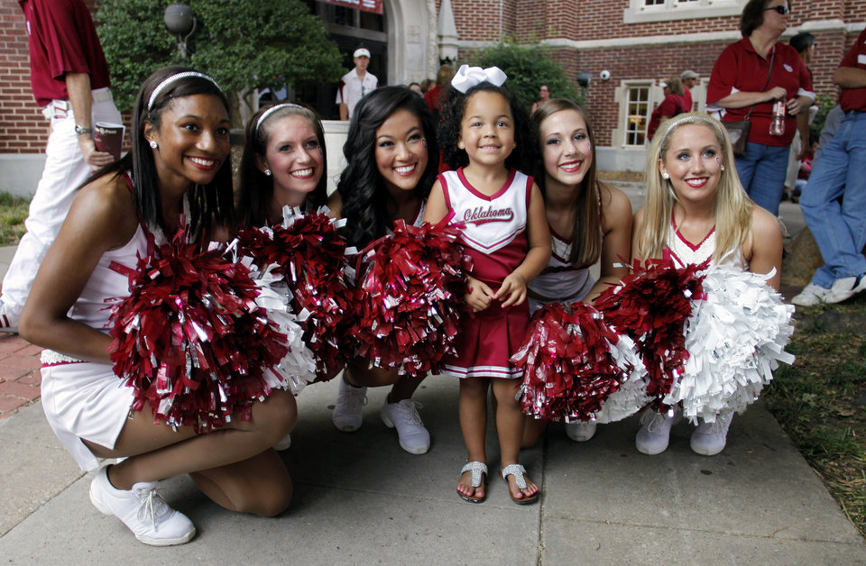 Photo - Solvei Modkins, 3 from Dallas, poses with OU Pom Pon squad members Brigette, Chrissy, Alicia, Molly and Katie in front of the Student Union before the college football game between the University of Oklahoma Sooners (OU) and the Tulsa University Hurricanes (TU) at the Gaylord Family-Memorial Stadium on Saturday, Sept. 3, 2011, in Norman, Okla. 