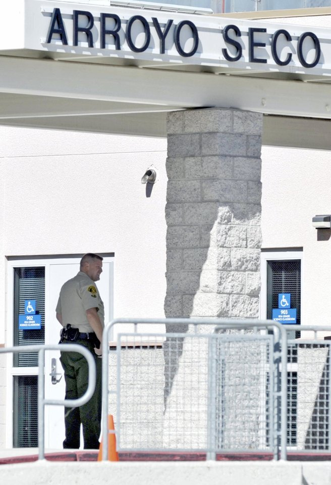 Photo -   A Los Angeles County sheriff's deputy is stationed at Arroyo Seco Junior High School in the Valencia neighborhood of Santa Clarita, Calif., Tuesday, Sept. 18, 2012. Eric Yee, accused of posting comments on ESPN's website saying he was watching kids and wouldn't mind killing them, was in jail Tuesday on $1 million bail after he was arrested at his home near the school for investigation of making terrorist threats, authorities said. (AP Photo/Santa Clarita Valley Signal, Jonathan Pobre) MANDATORY CREDIT