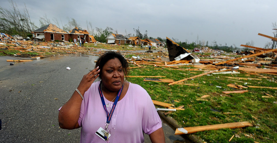 Tamisha Cunningham, who suffered a leg injury when her home was destroyed, looks over the damage while waiting for medical care, near Athens, Ala., Wednesday, April 27, 2011. Homes in the area were completely destroyed following a tornado that cut a path through Lawrence, Morgan and Limestone Counties. (AP Photo/The Decatur Daily, Gary Cosby Jr)