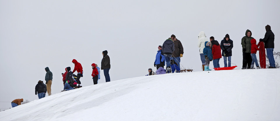 Photo - People stands at the top of a hill while sledding at Will Rogers Park in Oklahoma City, Saturday, Jan. 30, 2010.  Photo by Bryan Terry, The Oklahoman