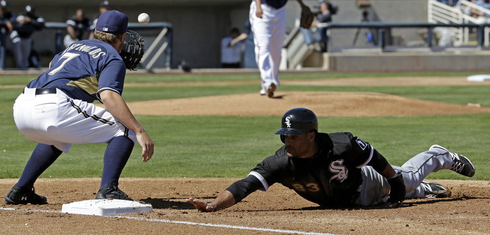 Photo - Chicago White Sox's Micah Johnson slides safely back to first with Milwaukee Brewers' Mark Reynolds covering on a pick off attempt during the first inning of an exhibition spring training baseball game Monday, March 10, 2014, in Phoenix. (AP Photo/Morry Gash)