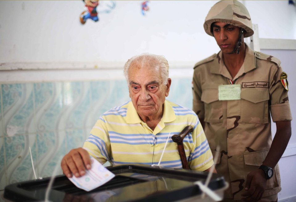 Photo - An Egyptian soldier watches a voter cast his ballot in the presidential election in Cairo, Egypt, Monday, May 26, 2014. This week's key vote is taking place against a backdrop of the turmoil that has roiled the country since the 2011 ouster of Hosni Mubarak and the government's crackdown against Morsi's Muslim brotherhood and its allies since last July.  (AP Photo/Mostafa Elshemy)