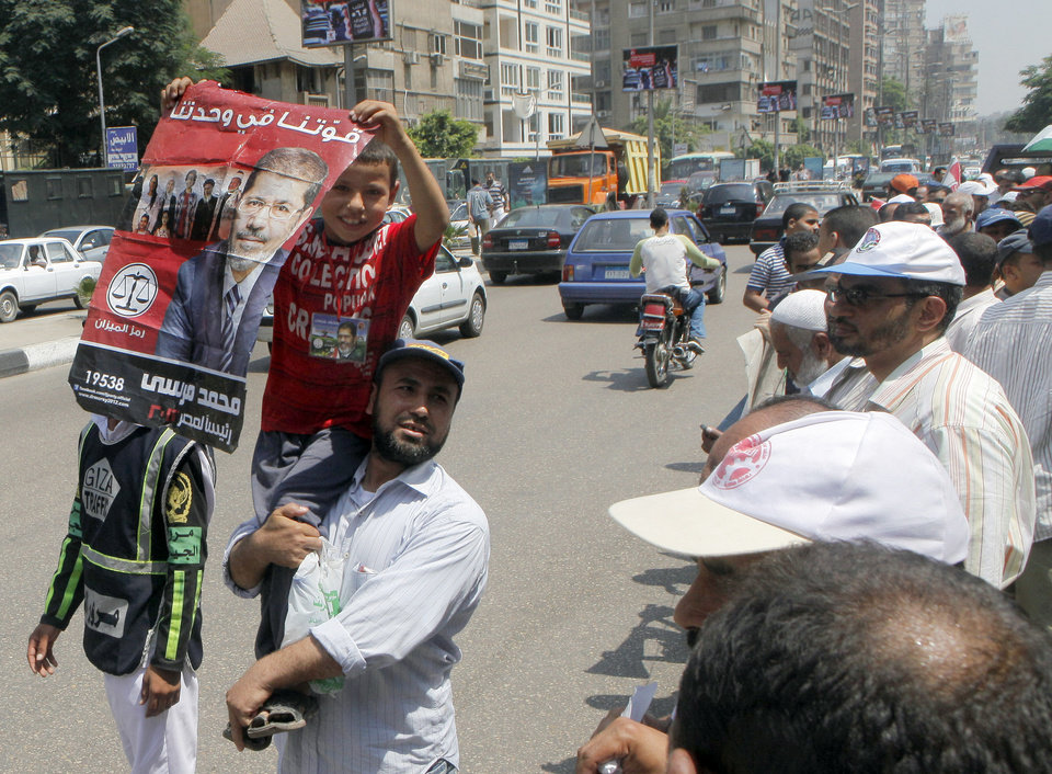 Photo -   An Egyptian supporter of President Mohammed Morsi carries his son holding a poster in Arabic that reads,