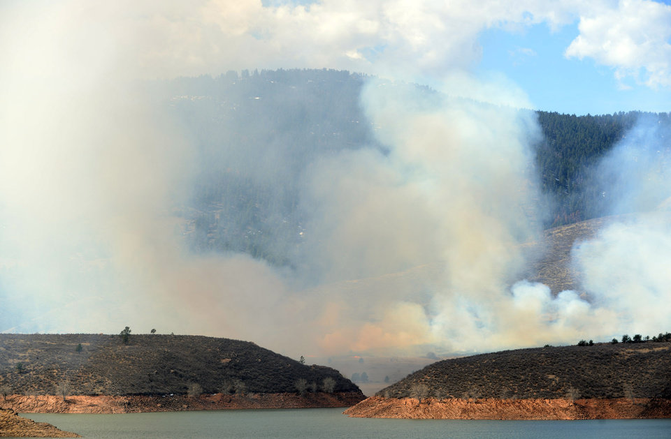 Photo - Smoke rises as a wildfire burns out of control at Horsetooth Reservoir west of Fort Collins, Colo., on Friday, March 15, 2013. The 40-acre wildfire burning in gusty winds and warm weather was threatening homes west of Fort Collins on Friday and prompted about 50 people to leave the area. (AP Photo/The Coloradoan, V. Richard Haro)