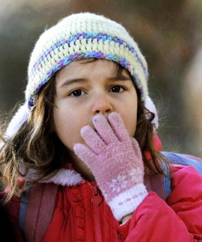 Dressed for today's winter weather, first grader Gwendolyn Ferris warms her mouth and nose with her glove covered hand as she arrives at East Side Elementary School on Key Blvd. in Midwest City. A weekend cold front brought sub-freezing thermometer readings and single-digit wind chill temperatures Monday morning. Dec. 10, 2012. Photo by Jim Beckel, The Oklahoman
