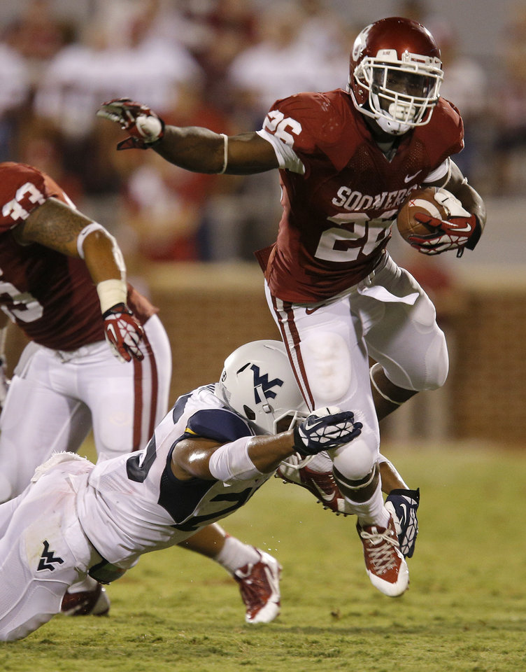 Photo - Oklahoma's Damien Williams (26) leaps past West Virginia's Darwin Cook (25)  during a college football game between the University of Oklahoma Sooners (OU) and the West Virginia University Mountaineers at Gaylord Family-Oklahoma Memorial Stadium in Norman, Okla., on Saturday, Sept. 7, 2013. Oklahoma won 16-7. Photo by Bryan Terry, The Oklahoman