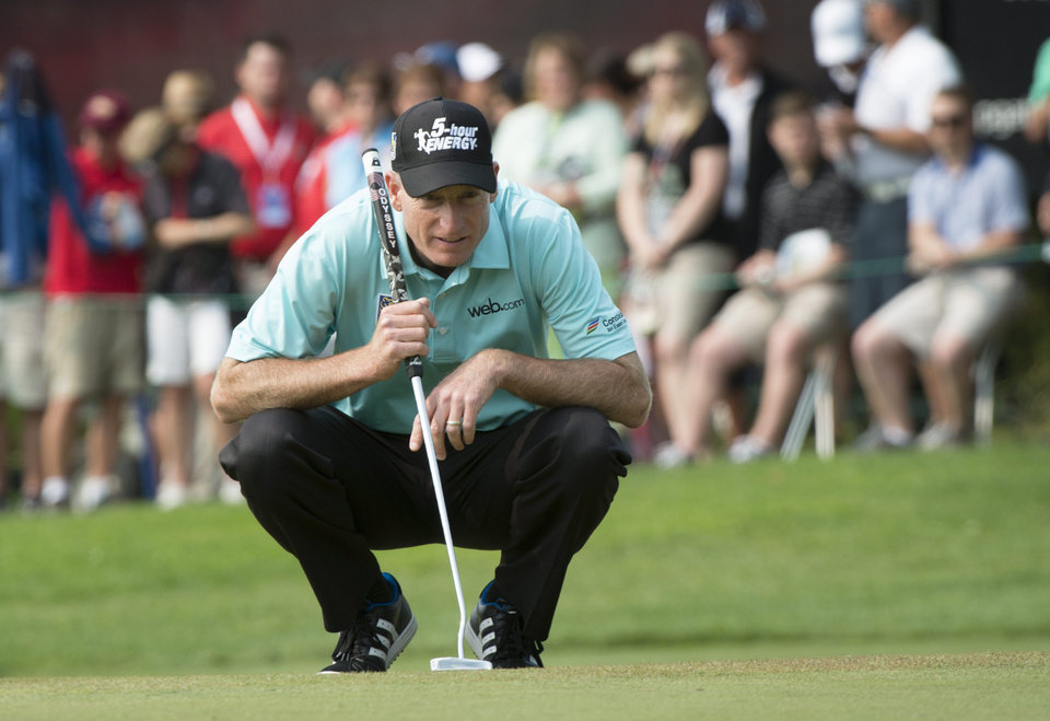 Photo - Jim Furyk checks his line on the 17th green during second round play at the Canadian Open golf championship Friday, July 25, 2014 in Montreal. (AP Photo/The Canadian Press, Paul Chiasson)