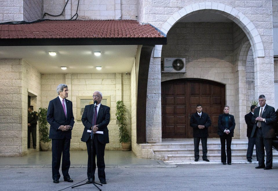 Photo - U.S. Secretary of State John Kerry, left, listens to Palestinian negotiator Saeb Erekat make a statement to the press after meeting with Palestinian President Mahmoud Abbas at the presidential compound in the West Bank city of Ramallah on Saturday, Jan. 4, 2014. Kerry said Israelis and Palestinians are committed to settling their differences and are working with