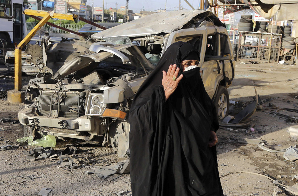 Photo - A woman looks at damage from a Saturday car bomb attack near a Kebab restaurant, in the mainly Shiite Habibiya neighborhood of Baghdad, Iraq, Sunday, May 11, 2014. A series of bombings on Saturday in Iraq killed and wounded scores of people, a day after army shelling killed many civilians and gunmen in the militant-held city of Fallujah, authorities said. (AP Photo/Karim Kadim)