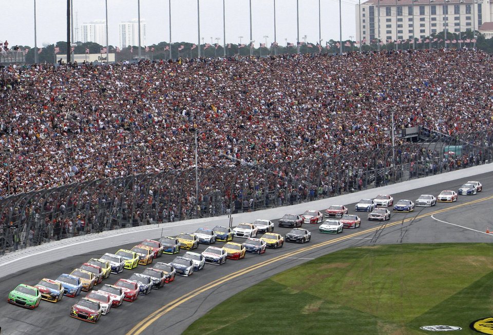 Photo - Danica Patrick, front left,and Jeff Gordon, front right, leads the pack to start the NASCAR Daytona 500 Sprint Cup Series auto race at Daytona International Speedway, Sunday, Feb. 24, 2013, in Daytona Beach, Fla. (AP Photo/David Graham)