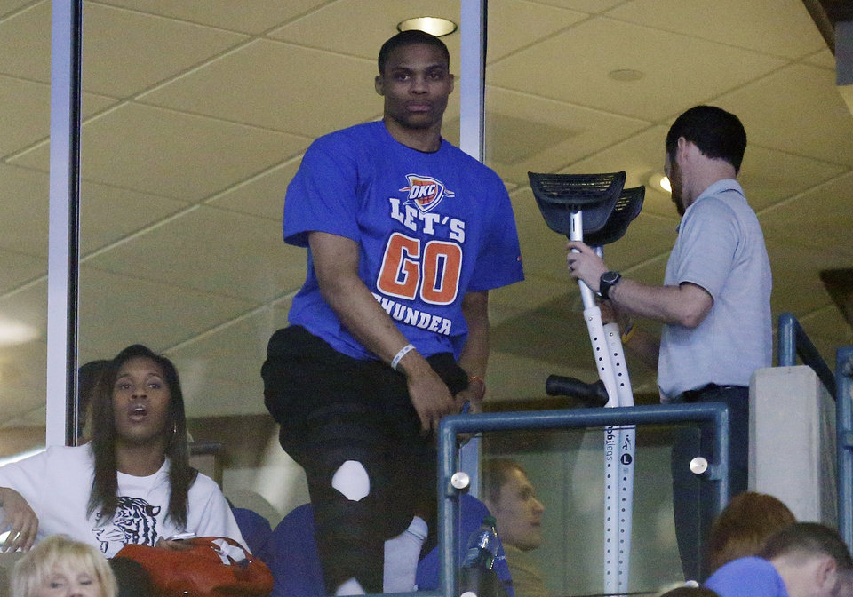 Oklahoma City Thunder guard Russell Westbrook, center, gets back on his crutches at the end of the second quarter of Game 5 of the Thunder's first-round NBA basketball playoff series against the Houston Rockets in Oklahoma City, Wednesday, May 1, 2013. Westbrook, who is injured, was watching the game from the suite level. (AP Photo/Sue Ogrocki)