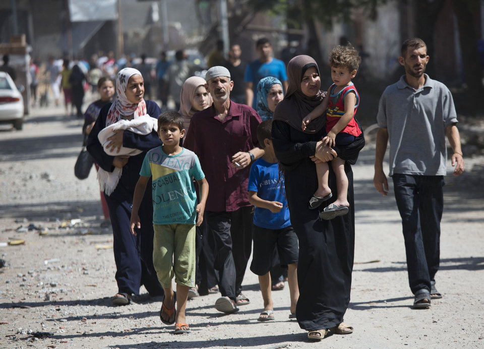 Photo - Palestinians return to the heavily bombed Gaza City neighborhood of Shijaiyah, close to the Israeli border, Friday, Aug. 1, 2014. A three-day Gaza cease-fire that began Friday quickly unraveled, with Israel and Hamas accusing each other of violating the truce. (AP Photo/Dusan Vranic)
