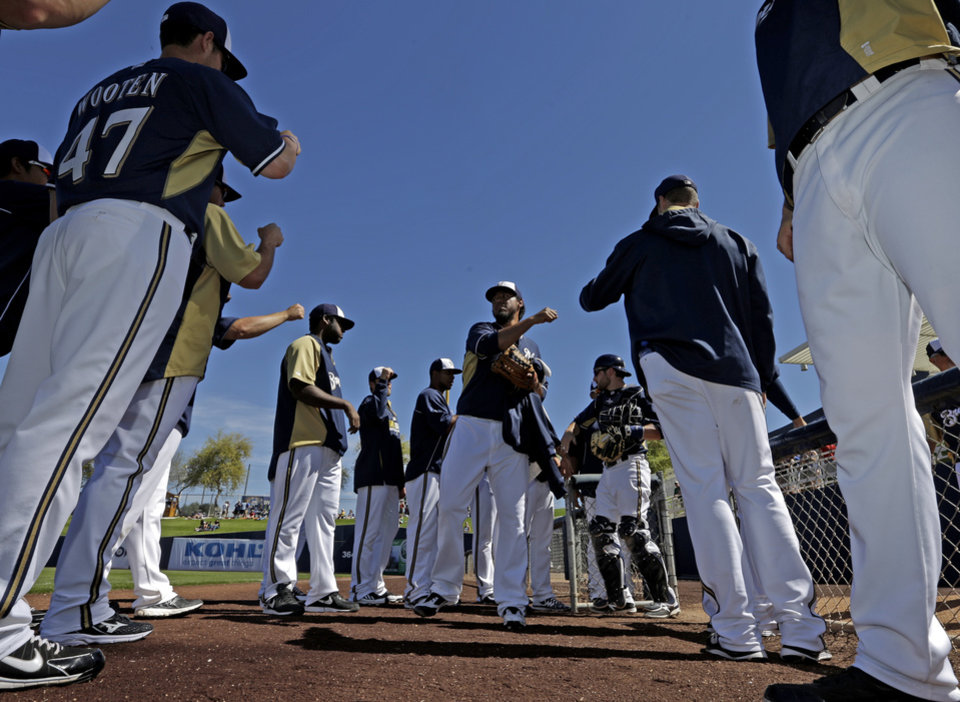 Photo - Players high five Milwaukee Brewers' Yovani Gallardo before his start of an exhibition spring training baseball game against the Chicago White Sox Monday, March 10, 2014, in Phoenix. (AP Photo/Morry Gash)
