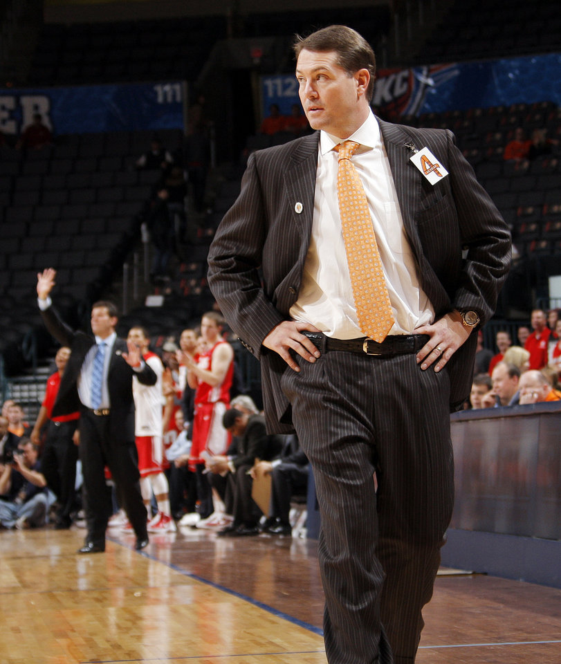Photo - OSU head coach Travis Ford watches his team in the second half during the Bill Russell men's college basketball game of the Ramada All-College Classic between the Oklahoma State University Cowboys and the University of New Mexico Lobos at the Chesapeake Energy Arena in Oklahoma City, Sunday, Dec. 18, 2011. UNM beat OSU, 66-56. Photo by Nate Billings, The Oklahoman
